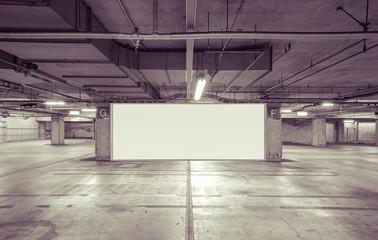 Parking garage underground interior with blank billboard..