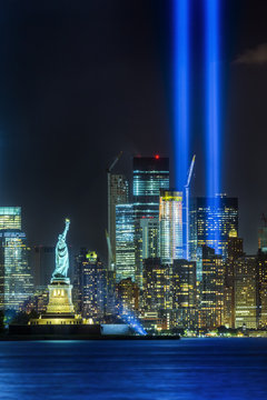 NEW YORK CITY - SEPTEMBER 11: The Statue of Liberty as seen in the evening of September 11, 2015 in New York City.  The 9-11 memorial lights can be seen in the background.