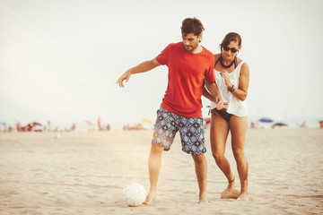 Young couple playing football on the beach
