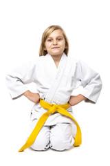 Pretty little girl in white kimono down on knees ready to fight