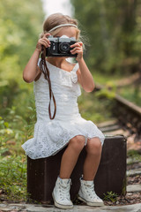 beautiful girl in a white dress sits on a vintage suitcase in a summer forest railway and pictures of forests around