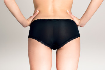 Female ass wearing black panties against white background