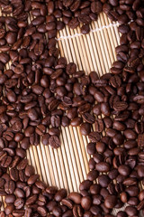 Coffee beans are laid out on a table on a straw or wooden stand.