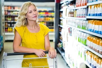Blond woman pushing cart choosing products