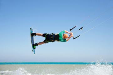 Junger Kitesurfer springt