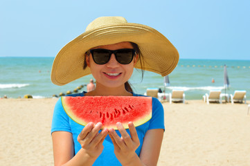 Beautiful young woman holding watermelon on beach