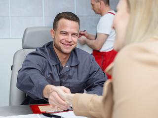 Customer and mechanic shake hands