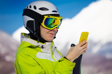 Skier woman look up in smart phone