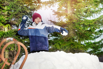 Boy throwing snowballs in sunny forest