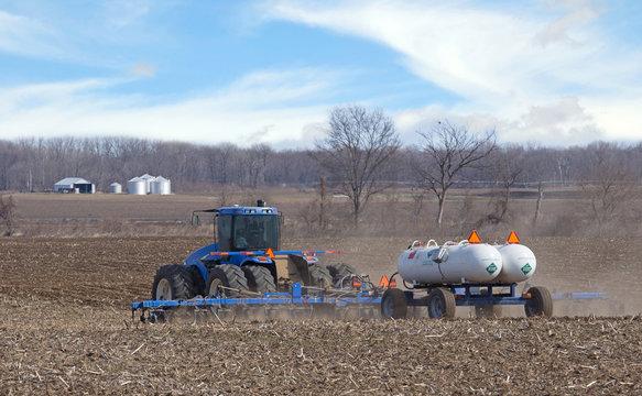 Tractor Pulling Anhydrous Ammonia Tanks Fertilizing a Farm Field