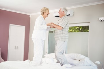Cheerful senior couple jumping on bed