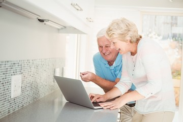 Senior couple laughing while using laptop in kitchen