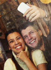 Young happy coupletaking selfie at cafe, view through a window