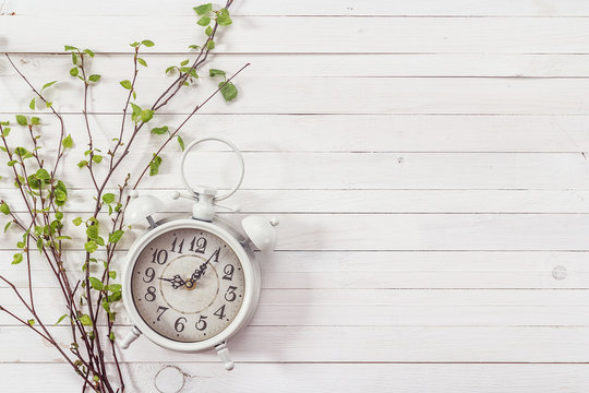 Background with white alarm clock and spring branch on white pai