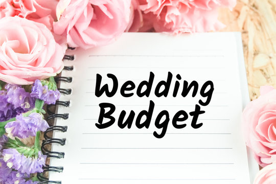 word wedding budget on note paper pink flower background