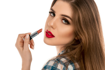 Close up portrait of young beautiful girl with lipstick in hand