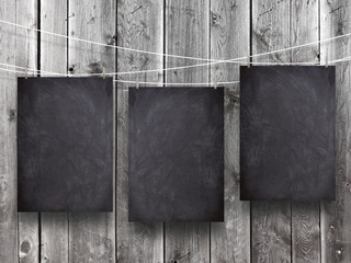 Close-up of three hanged blank blackboard frames with pegs against monochrome wooden background