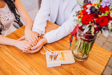 hands of bride and groom with wedding ring on wooden table with bouquet of roses