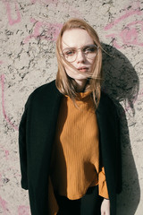 portrait of a beautiful young blond woman with glasses in the street