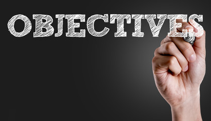 Hand writing the text: Objectives