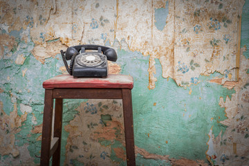 Old vintage phone on a chair stool in front of grunge wallpaper background
