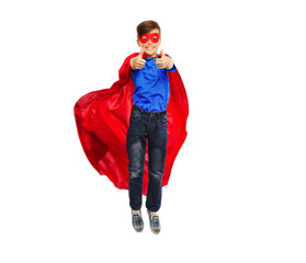 boy in super hero cape and mask showing thumbs up