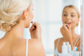 woman with lipstick applying make up at bathroom