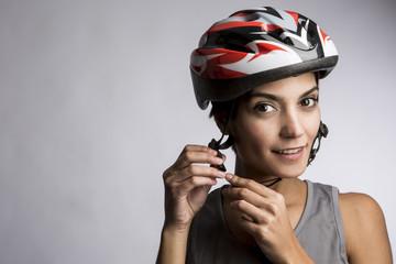 ritratto su inquadratura orizzontale di Donna Ciclista con casco su sfondo grigio