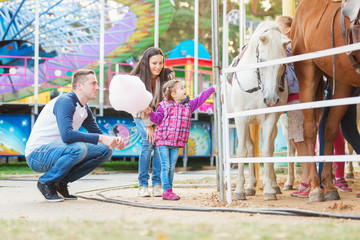 Family with daughter stroking pony in amusement park