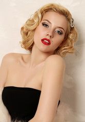 sexy woman with blond curly hair and bright makeup,wears fur