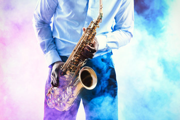 African American jazz musician playing the saxophone against colorful smoky background