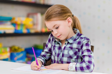 Adorable thoughtful little girl with blond hair sitting at white table and drawing with purple pencil
