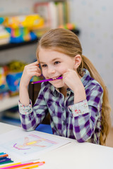 Funny little girl with blond hair sitting at white table and holding purple pencil in her mouth