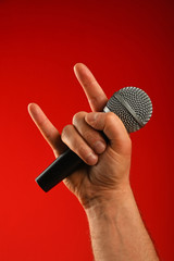 Man hand with microphone and devil horns over red