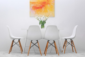 Modern dining room. White chairs and table with bouquet of flowers, abstract bright picture on the wall
