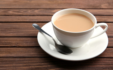 Porcelain cup of tea with milk on wooden background
