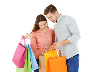 Young couple with colorful shopping bags isolated on white