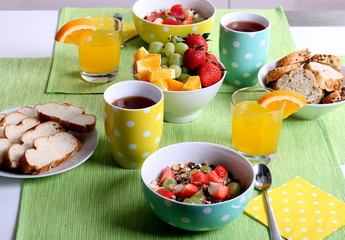 Healthy colorful breakfast: cereals with fresh fruits, wholemeal bread and fresh orange juice