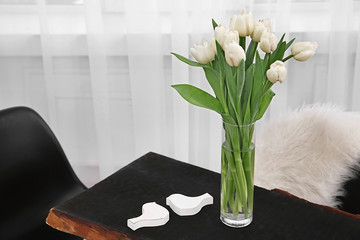 Beautiful bouquet of white tulips on wooden table