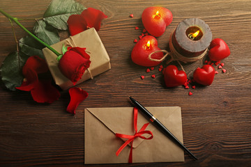 Gift card for Valentine's Day with red rose, pen and candles on wooden background