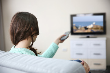 Young beautiful woman watching TV on a sofa at home