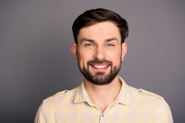 Portrait of attractive happy young man on gray background