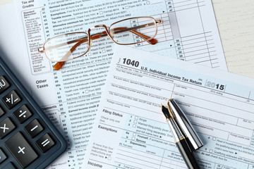 1040 Individual Income Tax Return Form for 2015 year with a pen to fill, calculator and metal rimmed glasses, close up