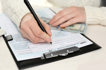 Woman  holding a pen and using filling in the individual income tax return on the white wooden table, close up