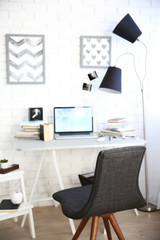 Workplace with laptop, table, lamp and chair in light room