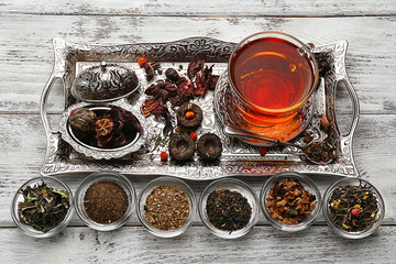 Tea concept. Glass cup of tea with different kinds of dry tea on vintage tray, close up
