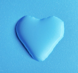 Heart made of water drop on blue background