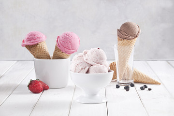 Various ice cream cones and cups are together.