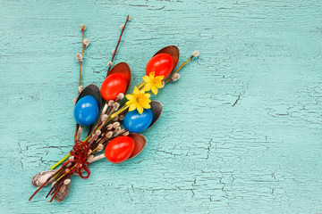 Red and blue Easter eggs, spoons, willow branch, flowers. Easter bouquet. Top view, copy space, Easter background