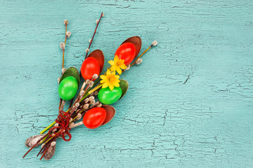 Easter bouquet. Red and green  Easter eggs, spoons, willow branch, flowers. Top view, copy space, Easter background